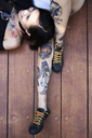 Happy woman lying on leg of tattooed girl friend on planks - IGGF00256