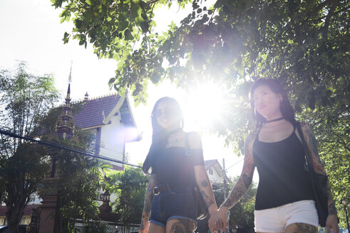 Tattooed lesbian couple holding hands in the street in summer - IGGF00259