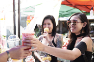 Woman buying a smoothie from a street vendor in Thailand - IGGF00265