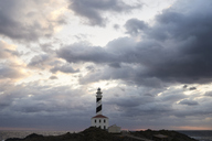 Spain, Balearic Islands, Menorca, Favaritx lighthouse surrounded by clouds in the morning - IGGF00271