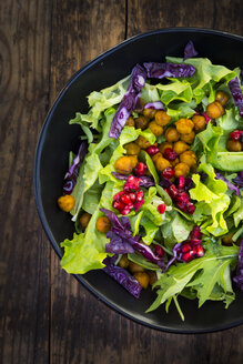 Bowl of mixed leaf salad with pomegranate seed, red cabbage and roasted curcuma chick peas - LVF06521