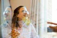 Smiling businesswoman behind glass pane - VABF01416