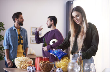 Friends preparing for football match with beer and snacks - ABIF00065