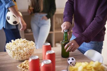 Football fan opening a bottle of beer - ABIF00068