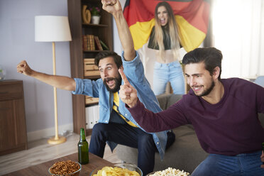 Excited German football fans watching Tv and cheering - ABIF00071