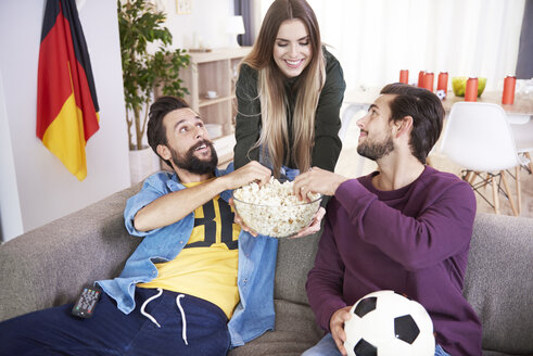 Woman serving snack to friends during football match - ABIF00077