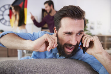 Man receiving a call during football match - ABIF00080