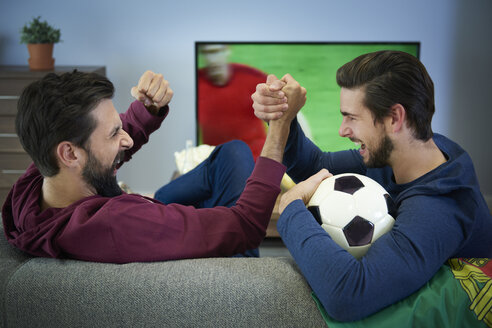 Two football fans watching Tv and cheering - ABIF00086