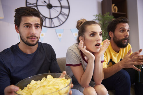 Excited friends sitting on the sofa watching Tv - ABIF00089