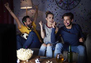 Excited friends sitting on the sofa watching Tv - ABIF00095