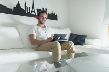 Smiling young man relaxing at home with his tablet - RAEF01950