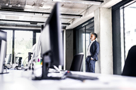 Mature businessman standing in office thinking - HAPF02514