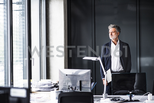 Mature businessman standing in office loooking out of window - HAPF02517