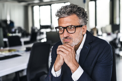 Portrait of serious mature businessman wearing glasses in office - HAPF02529