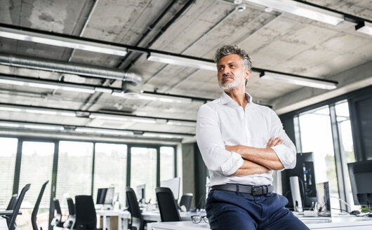 Mature businessman in office looking sideways - HAPF02535