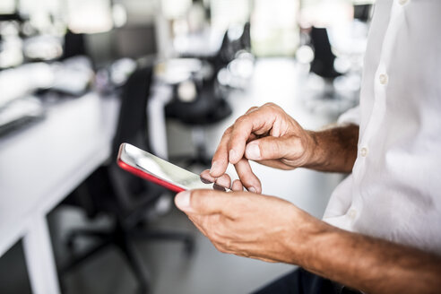 Close-up of businessman using cell phone in office - HAPF02538