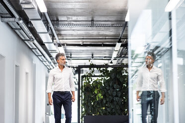 Mature businessman looking at his mirror image in glass pane - HAPF02544