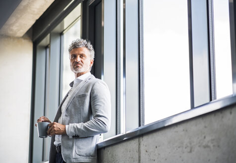 Mature businessman with coffee mug at the window - HAPF02547