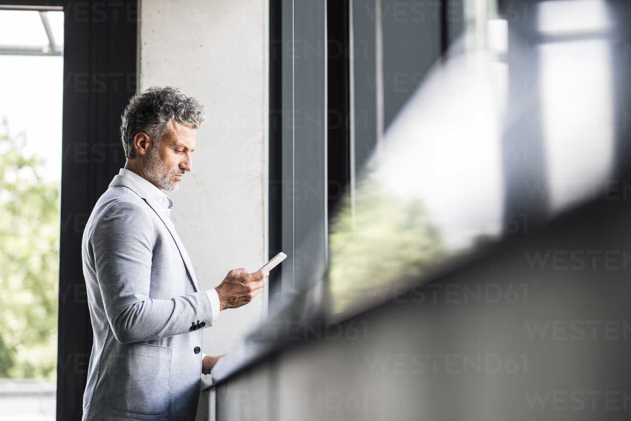 Mature businessman holding cell phone at the window - HAPF02550 - HalfPoint/Westend61