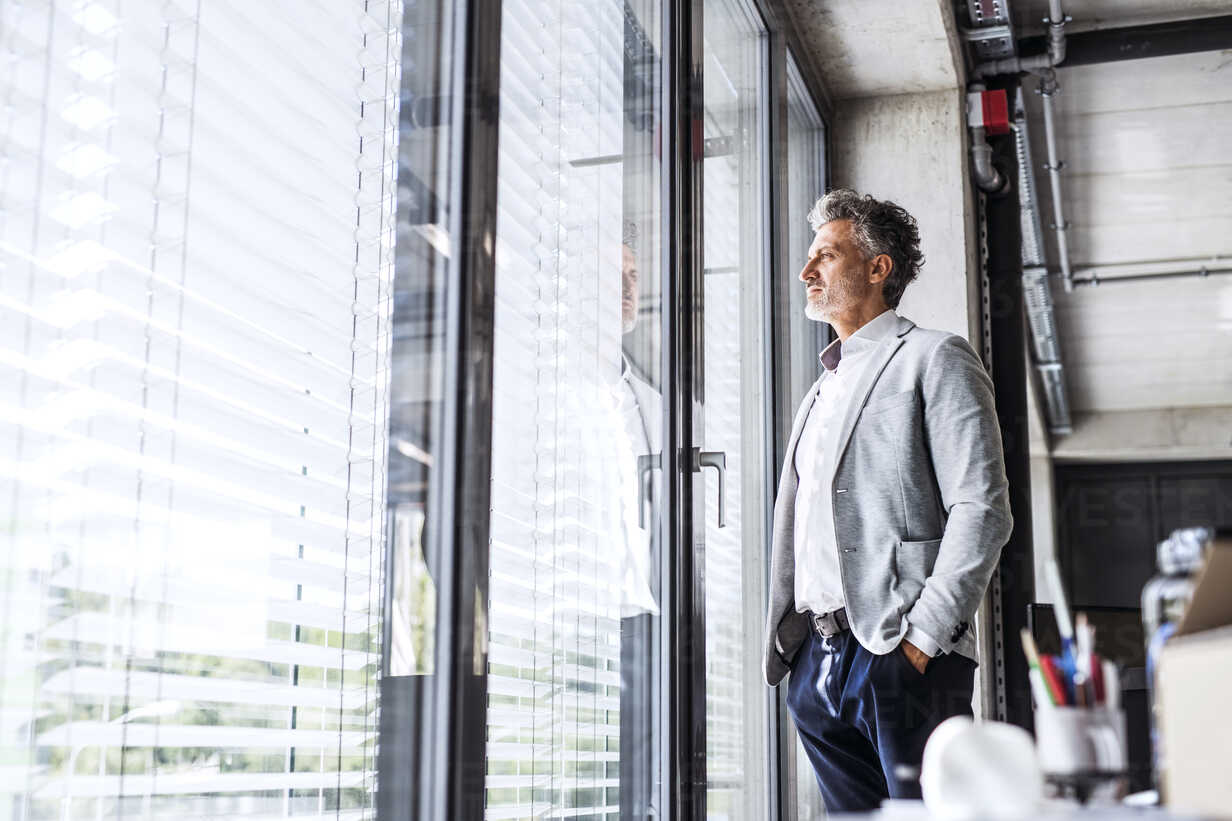 Mature businessman standing in office loooking out of window - HAPF02556 - HalfPoint/Westend61