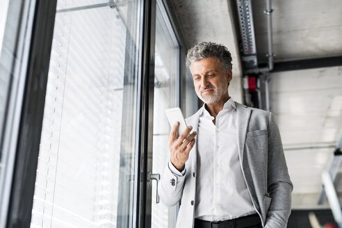 Smiling mature businessman standing at the window in office holding cell phone - HAPF02559