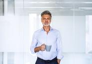 Portrait of confident mature businessman holding coffee mug - HAPF02574