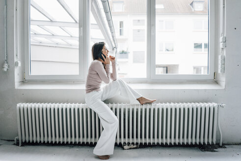 Laughing woman on the phone sitting on heater in a loft - MOEF00429