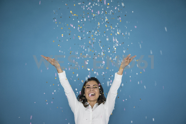 Portrait of laughing woman throwing confetti in the air - MOEF00432