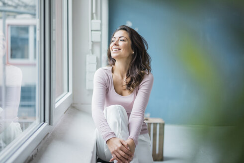 Happy woman sitting beside window sill looking out of window - MOEF00441