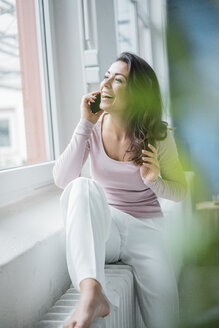 Portrait of laughing young woman on the phone sitting on heater in a loft looking out of window - MOEF00444