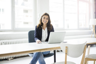 Portrait of happy businesswoman sitting at desk in the office working on laptop - MOEF00450