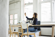 Laughing businesswoman sitting at desk in a loft taking selfie - MOEF00453