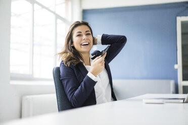 Portrait of laughing businesswoman with cell phone sitting at desk in the office - MOEF00456