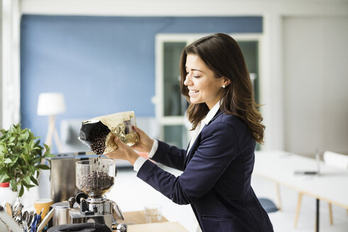 Businesswoman filling coffee beans into espresso machine - MOEF00465