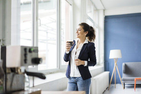 Happy businesswoman with glass of coffee in a loft looking out of window - MOEF00468