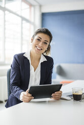 Portrait of happy businesswoman with tablet sitting at desk in the office - MOEF00471