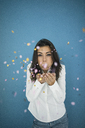 Portrait of young woman blowing confetti in the air - MOEF00474