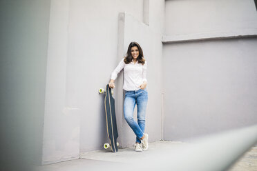 Smiling young woman with skateboard leaning against wall on terrace - MOEF00483