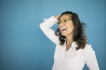 Portrait of laughing woman wearing glasses in front of blue background - MOEF00492