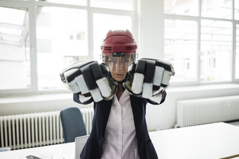 Portrait of businesswoman wearing ice hockey equipment - MOEF00495