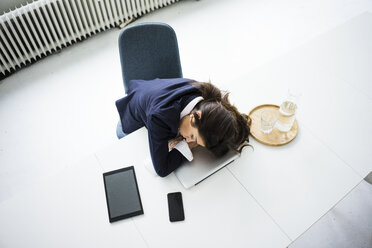 Overworked businesswoman sleeping on laptop in office, top view - MOEF00498
