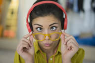 Portrait of woman with headphones and glasses pulling funny face - MOEF00504