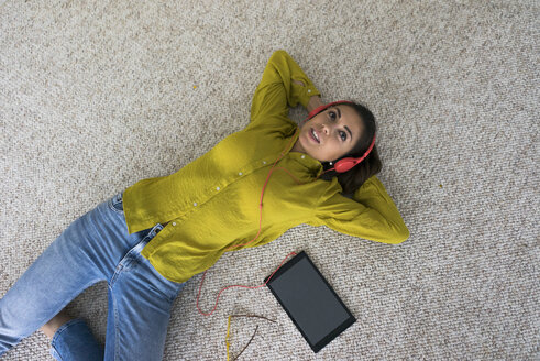 Portrait of young woman lying on the floor with headphones and tablet listening music, top view - MOEF00507