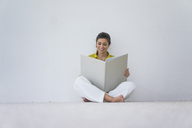 Smiling woman sitting on the floor reading oversized book - MOEF00513