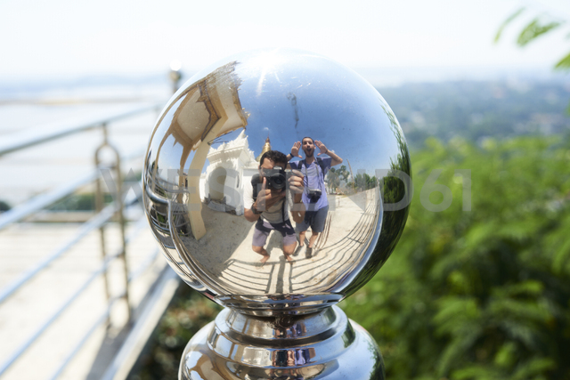 Two travelers having fun, reflected in a metallic fence knop - IGGF00280