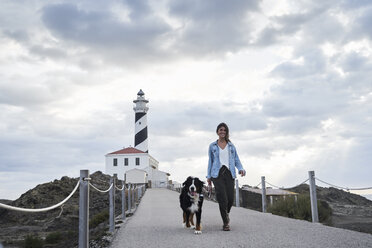 Spain, Menorca, Bernese mountain dog walking together with his owner outdoors at lighthouse - IGGF00289