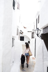 Spain, Menorca, Bernese mountain dog walking next to his dog owner in a small white village in summer - IGGF00306