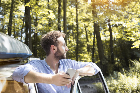 Young man with cell phone at car in forest - FKF02791