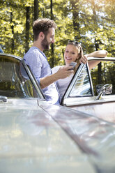Smiling young couple with cell phone at car in forest - FKF02794