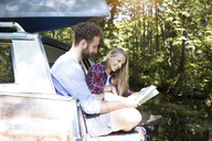 Smiling young couple with map and canoe in car at a brook - FKF02797